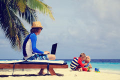 Father working on laptop while kids play at beach Royalty Free Stock Photos