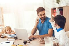 Father works at home and engaged in the upbringing of sons. Man works and looks after the children. The father works at home and is engaged in the upbringing of royalty free stock images