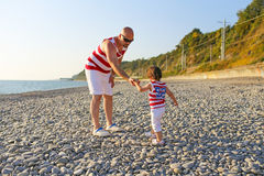 Father and 2 years son in similar clothes walk on the seaside Stock Photo