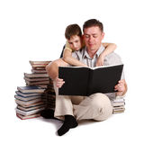Father and Young boy reading books. Father and Young boy sitting on a pile of books reading against a white background royalty free stock images