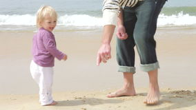 Father And Young Daughter Collecting Seashells On Shoreline stock footage