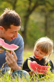 Father and young daughter eat watermelon in nature Stock Image