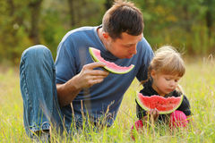Father and young daughter eat watermelon in nature Stock Images