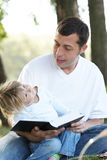 Father with a young daughter read the Bible in nature Royalty Free Stock Photography