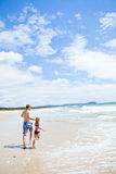 Father and young daughter running along beach Stock Image