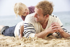 Father And Young Daughter Sitting On Beach Together Royalty Free Stock Photo