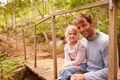 Father and young daughter sitting on a bridge in a forest stock image