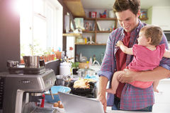Father With Young Daughter Using Laptop In Kitchen Royalty Free Stock Photo