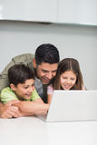 Father with young kids using laptop in kitchen Stock Photo