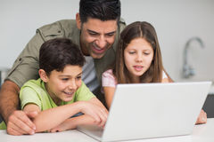 Father with young kids using laptop in kitchen Stock Photos