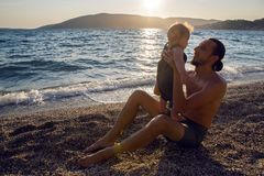Father with a young son on beach. With sunset Royalty Free Stock Images