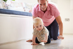 Father And Young Son Crawling Around Room Together Stock Photos