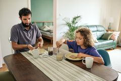 Father and young son eating lunch together at home stock photos
