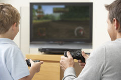 Father And Young Son Playing With Game Console. At Home Royalty Free Stock Images