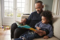 Father And Young Son Reading Book Together At Home stock photography