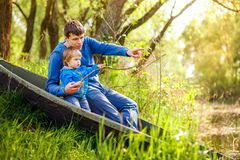 Father and young son are sitting in a boat on the lake and fishing. royalty free stock photography
