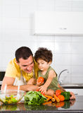 Fatherhood. Concept: happy young father playing with toddler son in kitchen Royalty Free Stock Image
