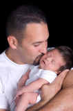 Fatherhood. Handsome father kisses his sleeping newborn baby boy Stock Photo