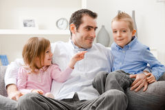Fatherhood. Family portrait, father and little siblings sitting together on couch, smiling stock photography