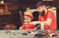 Fatherhood concept. Boy, child busy in protective helmet learning to use hammer with dad. Father with beard teaching. Little son to use tools, hammering royalty free stock images