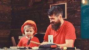 Fatherhood concept. Boy, child busy in protective helmet learning to use hammer with dad. Father, parent with beard royalty free stock images