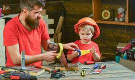 Fatherhood concept. Boy, child busy in protective helmet learning to use handsaw with dad. Father, parent with beard stock images