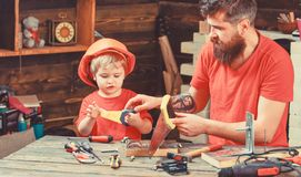 Fatherhood concept. Boy, child busy in protective helmet learning to use handsaw with dad. Father, parent with beard. Teaching little son to sawing while son royalty free stock photos