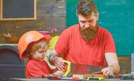 Fatherhood concept. Boy, child busy in protective helmet learning to use handsaw with dad. Father, parent with beard stock photos