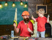 Fatherhood concept. Boy, child cheerful playing and learning to use tools with dad. Father, parent with beard in. Protective helmet teaching little son to use Royalty Free Stock Photography