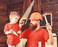 Fatherhood concept. Father, parent with beard in protective helmet teaching son to use different tools in school royalty free stock photos