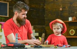Fatherhood concept. Father, parent with beard teaching little son to sawing while son play with toy saw. Boy, child busy. In protective helmet learning to use stock photos