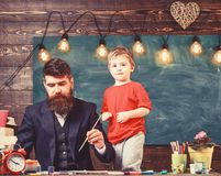 Fatherhood concept. Talented artist spend time with son. Teacher with beard, father teaches little son to draw in stock photo