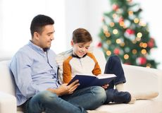 Happy father and son reading book at christmas Stock Photography