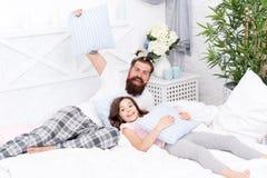 Fatherhood feliz Moderno farpado do homem com os rabos de cavalo coloridos e a filha do penteado criançola nos pijamas Indiv?duo  foto de stock