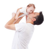 Fatherly love. Happy young men holding and kissing a 4-5 months old baby, isolated on white Royalty Free Stock Image