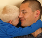 Fatherly love. A portrait of a young boy hugging his smiling father Stock Images