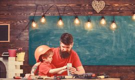 Fathers assistant concept. Father with beard teaching little son to use tools in classroom, chalkboard on background royalty free stock images