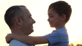 Fathers and children . Happy father and son hug each other. The child hugs his father. The silhouette of a happy family