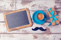 Fathers day background with chalkboard, coffee cup and gift box on wooden table. View from above. Royalty Free Stock Photos