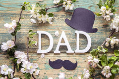 Fathers day background with letters DAD, paper hat, mustache and. Apple blossom. Top view. Happy fathers day concept Stock Photography