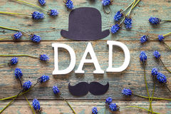 Fathers day background with letters DAD, paper hat, mustache and. Blue flowers. Top view. Happy fathers day concept royalty free stock photos