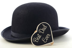 Fathers Day Bowler Hat. Fathers Day concept with mens black bowler hat and Best Dad Ever blackboard greeting on a white wood table royalty free stock photography