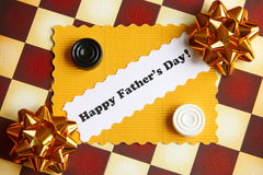 Fathers Day Card on Chessboard - Stock Photo. Fathers Day Card with Happy Fathers Day text and draughts on chessboard background Royalty Free Stock Photos