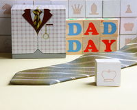 Fathers Day Card on Chessboard - Stock Photo. Fathers Day Card with Gift Box, Tie, Dad Day text on wooden cubes on chessboard background Royalty Free Stock Photo
