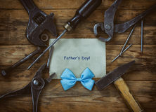 Fathers Day card, old tools on wooden table. Sheet of paper, blue bow stock photo