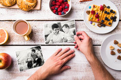 Fathers day composition. Black-and-white photos, breakfast meal. Fathers day composition. Hands of unrecognizable men holding black and white pictures of him and stock photo