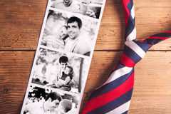 Fathers day composition. Black-and-white photos, tie. Wooden bac. Fathers day composition. Black and white pictures of father and son, colorful tie. Wooden royalty free stock images