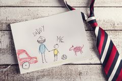 Fathers day composition. With childs drawing and colorful tie laid on wooden desk backround stock images