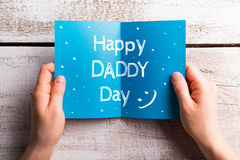 Fathers day composition. Hands of dad holding greeting card Royalty Free Stock Photo