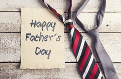 Fathers day composition. Happy fathers day sign on paper and colorful ties laid on wooden floor backround Stock Photography